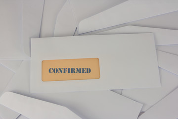 confirmed announcement from white envelope on heap of envelopes