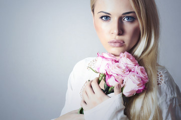 Beautiful Woman with Flowers.Blond girl and roses.bouquet