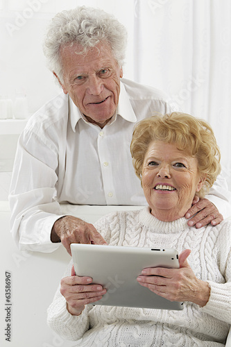 Happy senior couple surfing the internet with laptop computer