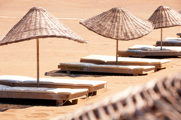 Sunbeds and parasols on sandy beach.