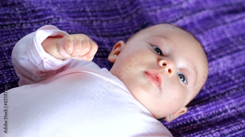 A happy baby plays on a purple blanket