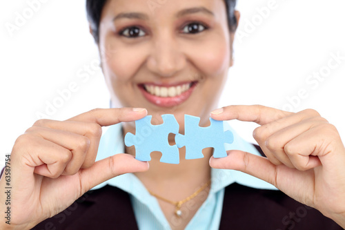 Business woman joining two jigsaw puzzle pieces