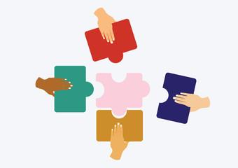 hands assembling jigsaw puzzle