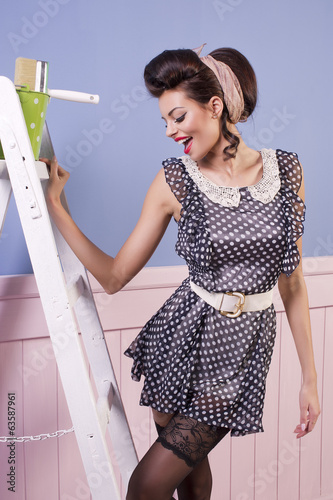 Beauty pinup girl with equipment for painting