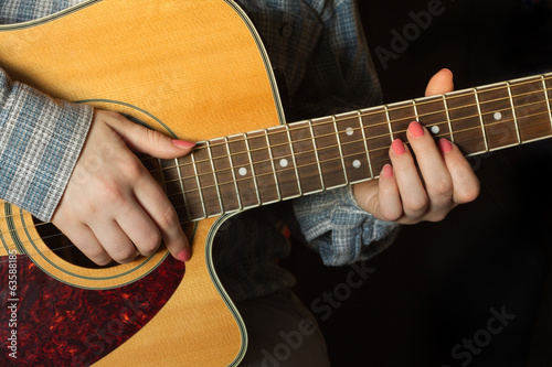 Girl  playing an acoustic guitar closeup