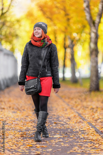 Portrait of beautiful red-haired young woman walking in autumn p