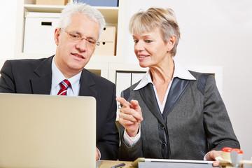 Geschäftsfrau hilft Kollegen am Computer