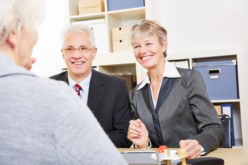 Geschäftsleute reden mit Frau über Finanzen