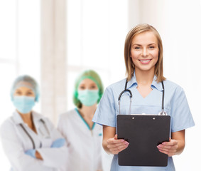 smiling female doctor or nurse with clipboard