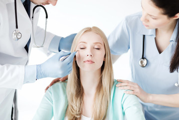 plastic surgeon and nurse with patient