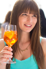 Young smiling woman drinking aperol in turquoise tank top