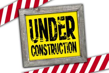 Schild mit Ziegelsteinmeuer und Under Construction