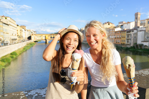 Happy women friends eating ice cream in Florence