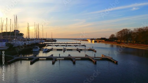 Sunset on the river pier with yachts in the evening.
