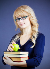 Educated woman, holding pile of books and an apple