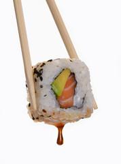 Sujetando sushi roll con salsa de soya.Comida japonesa.