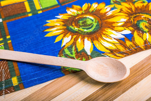 Kitchen towel and   wooden spoon on wooden board