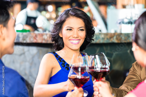 Asian Friends toasting with wine in restaurant