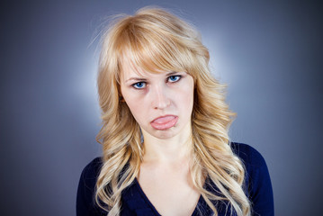 Annoyed, tired woman sticking her tongue out