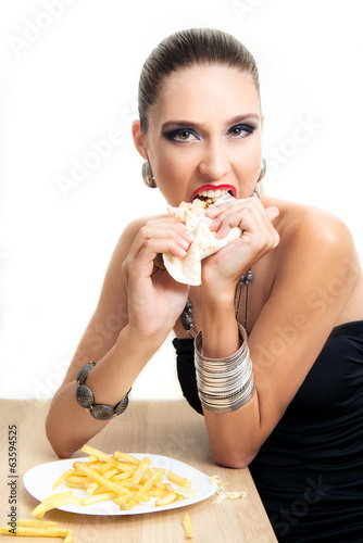 Beautiful glamour woman is eating fast food