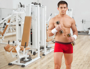 handsome young man wearing red shorts lifting weights and lookin