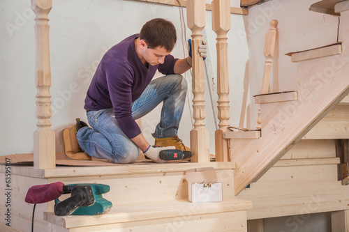 young worker sitting on floor and drilling with cordless drill