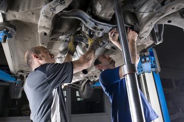 Two Repairmen Fixing a Car