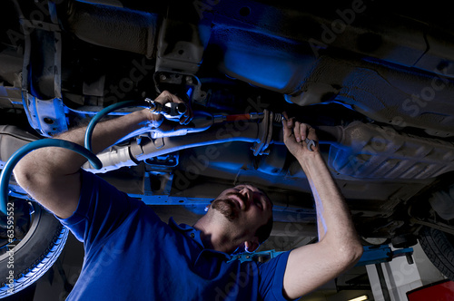 Car repairman working with air spanner