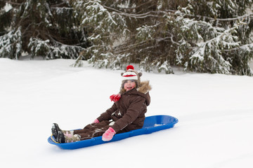 Girl sitting on toboggan sled in the snow in the winter by pine