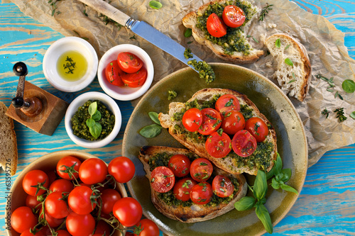 Bruschetta with fresh cherry tomatoes and aromatic herb pesto
