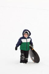 A boy walking up a sledding hill with a round sled
