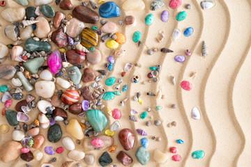 Pebbles, gemstones and shells on beach sand