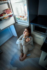 woman sitting on floor and looking at fridge at night