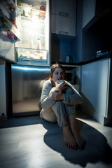 young woman eating next to refrigerator at night