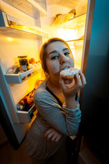 portrait of woman biting donut at night near fridge