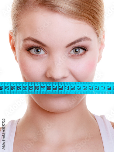 Fitness girl covering her mouth with measuring tape isolated