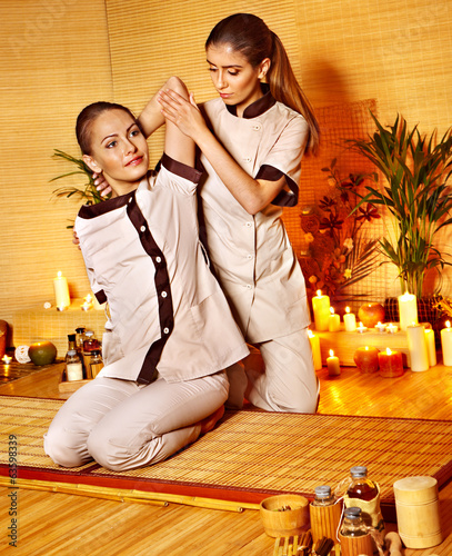 Woman getting massage in bamboo spa..