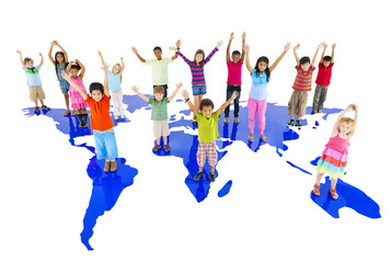 Group of children hands up and standing on the world map