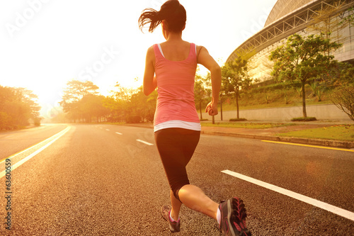 young fitness woman running at sunrise road