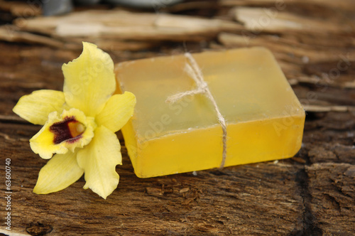 yellow orchid and soap on a grunge wood background