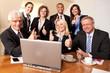 Gemischtes Team am Schreibtisch mit Daumen hoch