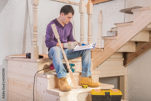 young handsome man sitting on floor holding clipboard with bluep