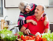 happy elderly couple cooking with vegetables