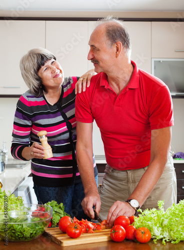 happy elderly couple cooking  lunch