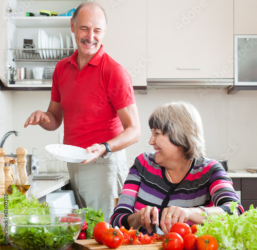 happy senior man and mature woman  doing chores