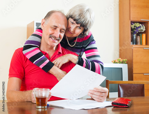 Cheeful mature man with wife reading  documents