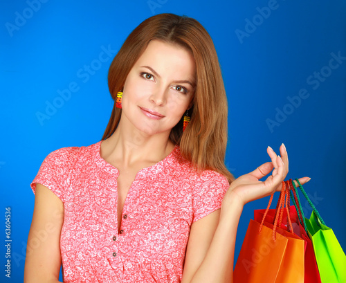 Young girl holding shopping bag, isolated on blue background.