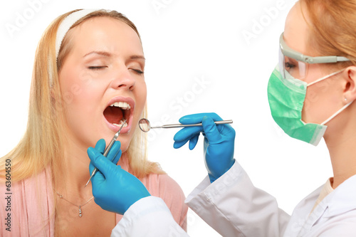 dentist at work on woman patient in office.