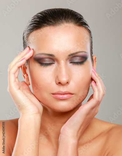 Young woman touching her face isolated on grey background.