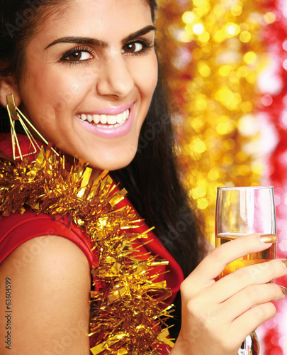Beautiful young woman drinking champagne at christmas party.